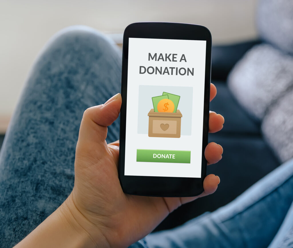 Girl holding smart phone with donation concept on screen