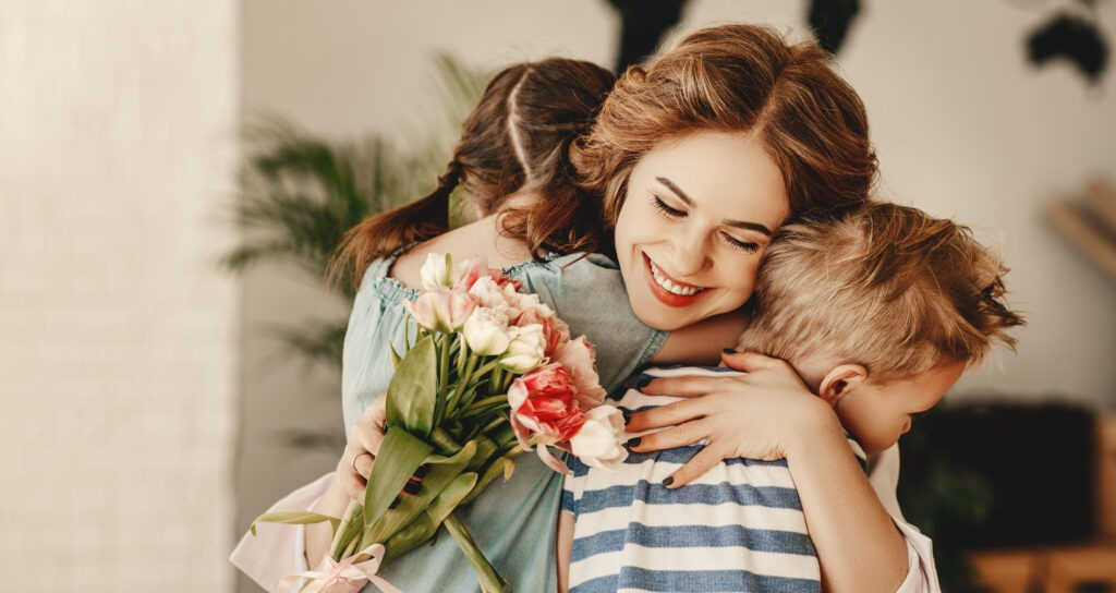 Happy Mothers Day! Children boy and girl congratulate smiling mother, hugs her  and give her flowers   bouquet of tulips during holiday celebration in kitchen at home